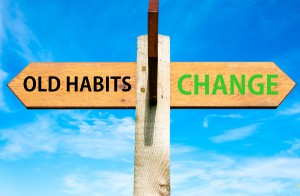 Wooden signpost with two opposite arrows over clear blue sky Old Habits versus Change messages Lifestyle change conceptual image